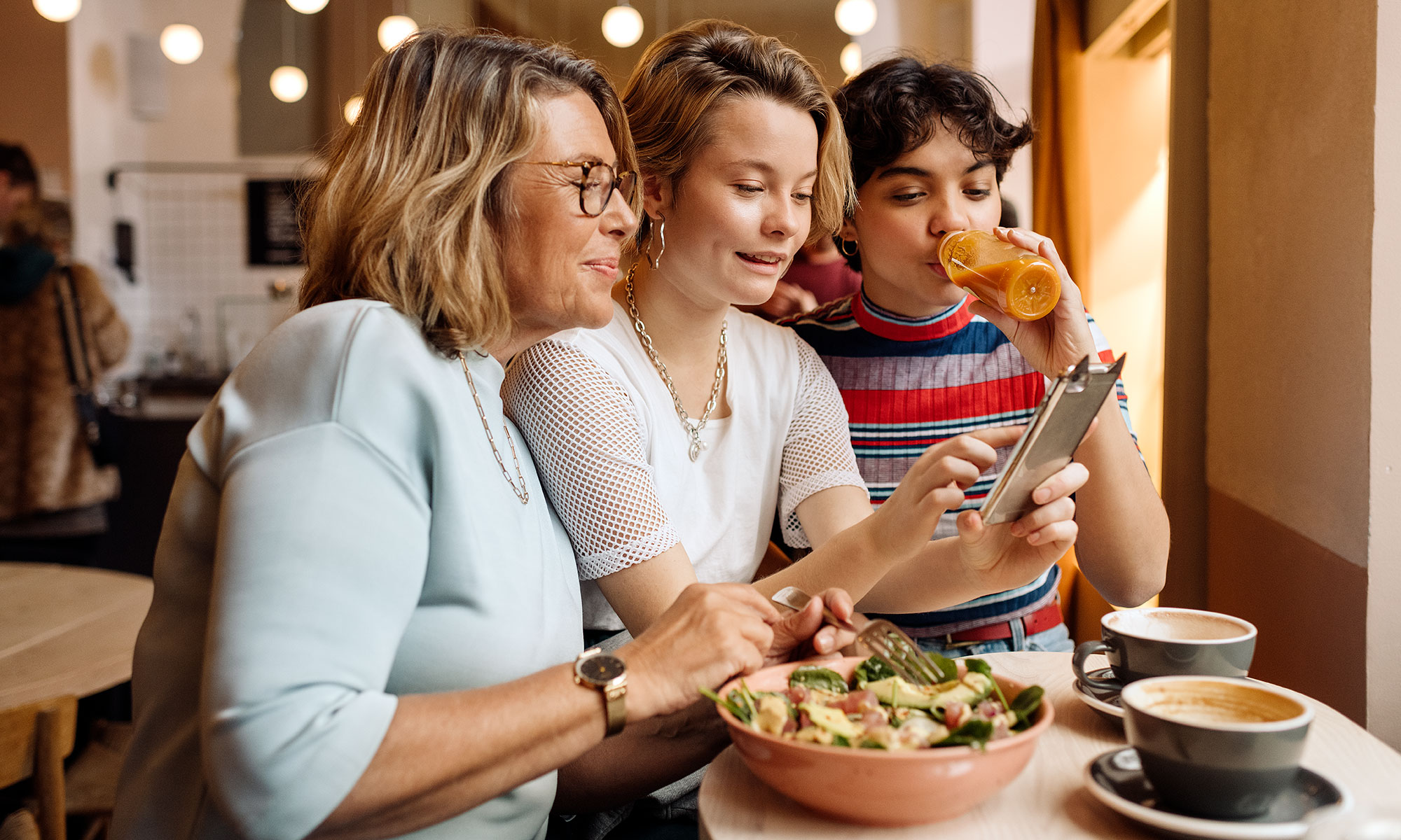 Three women having lunch and looking at a smart phone.